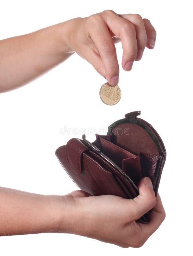 La mano pone una moneda en el monedero imágenes de archivo libres de regalías