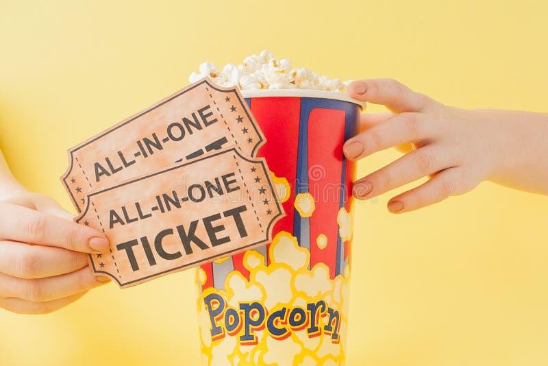 La mano prende i biglietti ed il popcorn di un film da una tazza di carta su un fondo giallo La donna mangia il popcorn Concetto  fotografia stock
