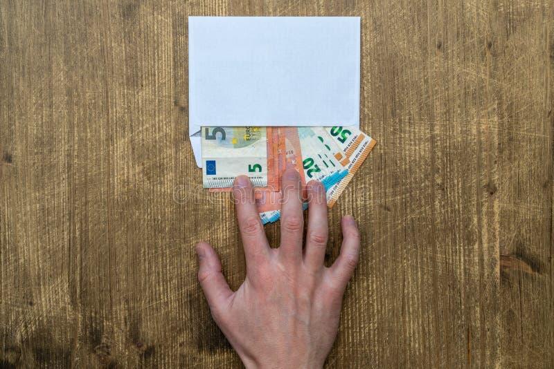 La mano prende una busta con soldi immagine stock libera da diritti