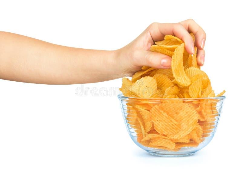 La mano prende una manciata di patatine fritte da una ciotola di vetro immagini stock