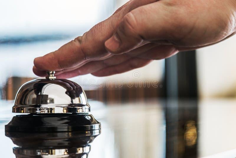 La mano presiona la campana del servicio en la recepción en hotel imágenes de archivo libres de regalías