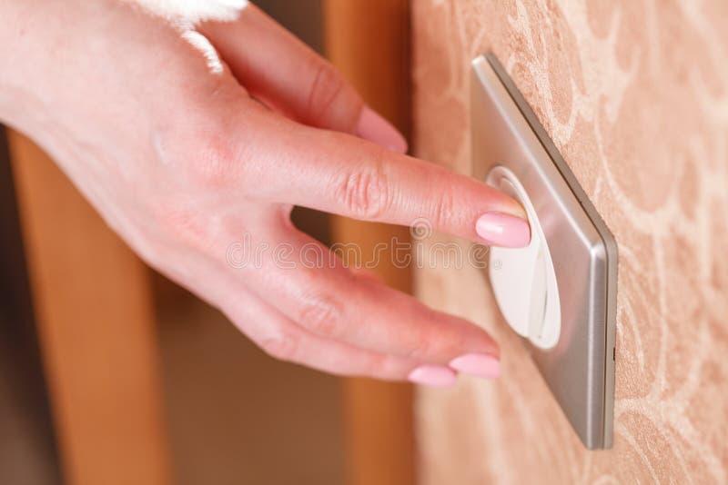 La mano presiona el interruptor de la luz en la pared imagenes de archivo