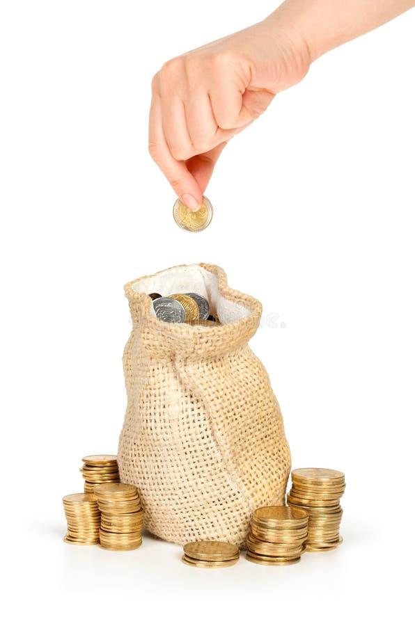 La mano puso la moneda en bolso con el dinero fotografía de archivo libre de regalías