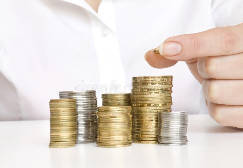 La mano puso la moneda en las monedas de la pila imagen de archivo libre de regalías