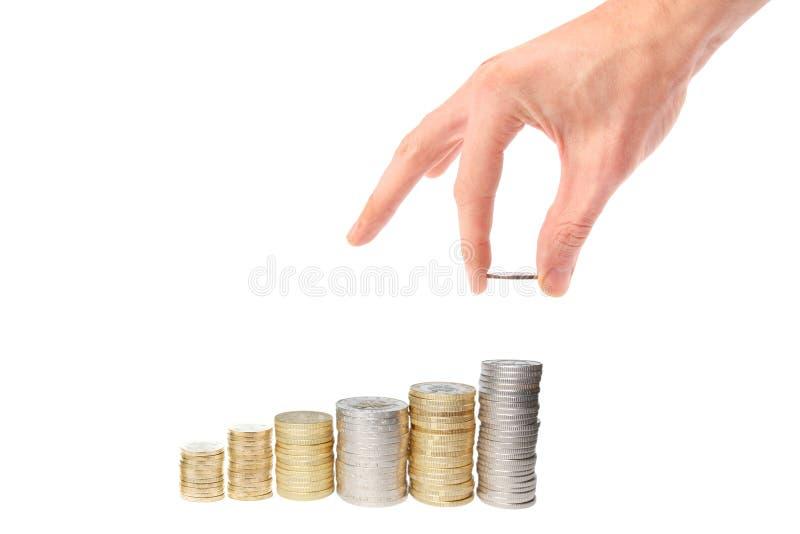 La mano puso la moneda a la escalera del dinero imagenes de archivo