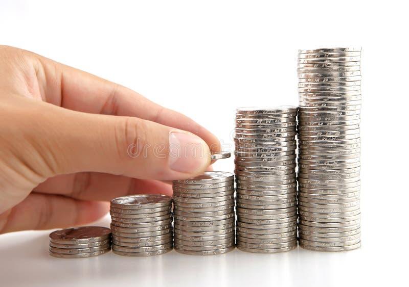 La mano puso la moneda a la escalera del dinero fotografía de archivo