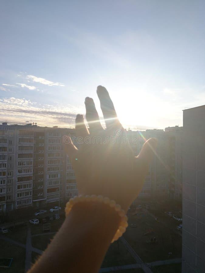 La mano que alcanza hacia el sol en el cielo a la hora de la puesta del sol imagen de archivo libre de regalías