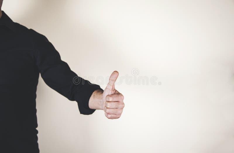La mano que muestra los pulgares sube la muestra imagen de archivo libre de regalías