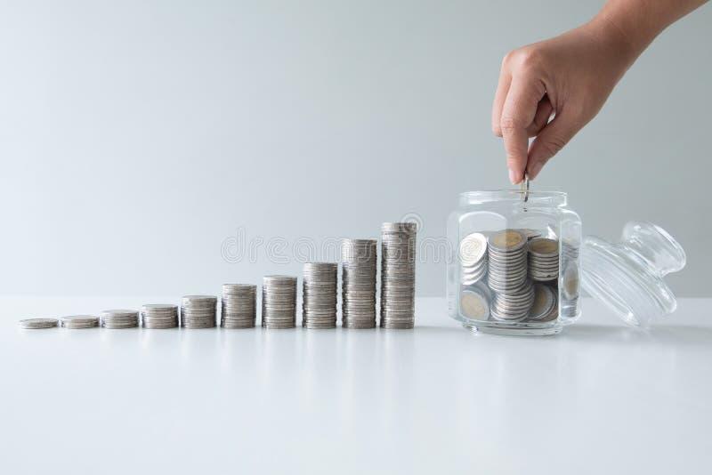 La mano que pone la moneda en el banco de la botella de cristal con el gráfico de barra del crecimiento de las monedas, intensifi fotografía de archivo libre de regalías
