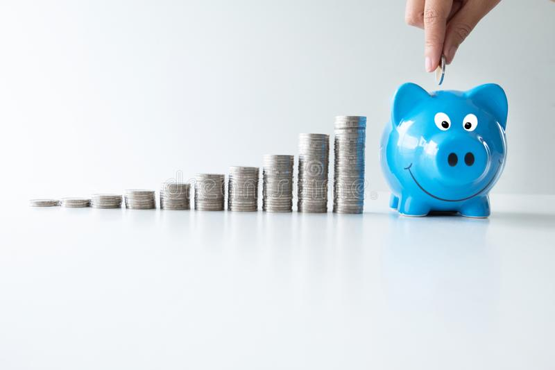 La mano que pone la moneda en la hucha azul con el gráfico de las monedas, intensifica comienzo encima del negocio al éxito, ahor fotografía de archivo
