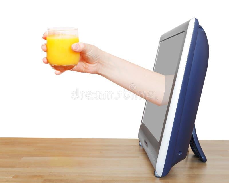 La mano que se sostiene de cristal con el zumo de naranja inclina hacia fuera la TV foto de archivo libre de regalías