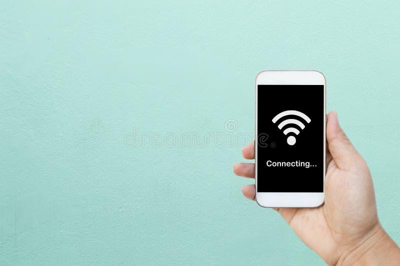 La mano que sostiene el teléfono elegante/el teléfono móvil blanco con wifi conecta en la pantalla negra foto de archivo