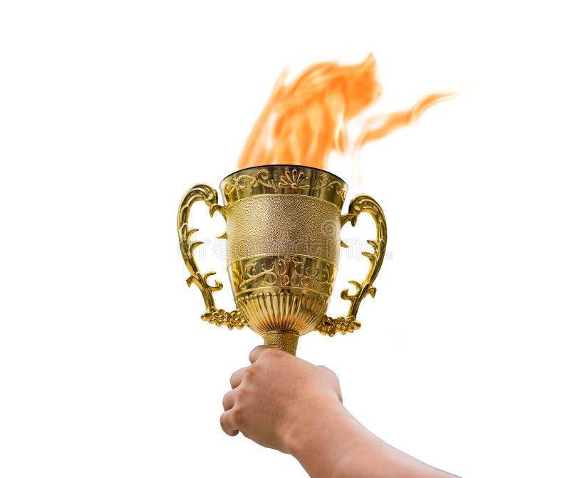 La mano que sostiene la taza de oro del trofeo con brillar intensamente de la llama aumenta para arriba en vagos foto de archivo