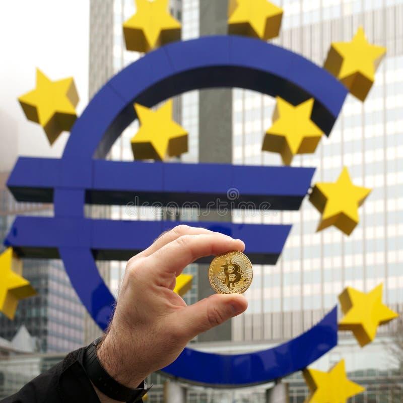 La mano que sostiene una moneda de Bitcoin al lado del euro firma adentro Francfort Alemania imagen de archivo