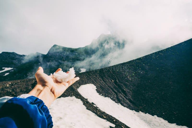 La mano que toca nieve a través de las montañas de Sochi de la niebla de las nubes ajardina verano emocional de la aventura del c fotos de archivo libres de regalías