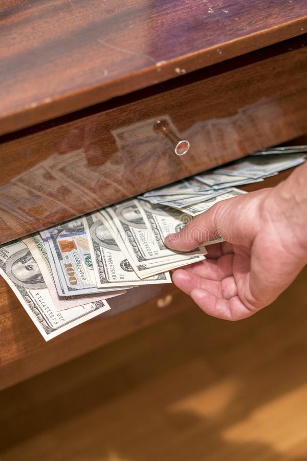 La mano que toma dólares del cajón del escritorio Cientos cuentas en cajón del escritorio foto de archivo