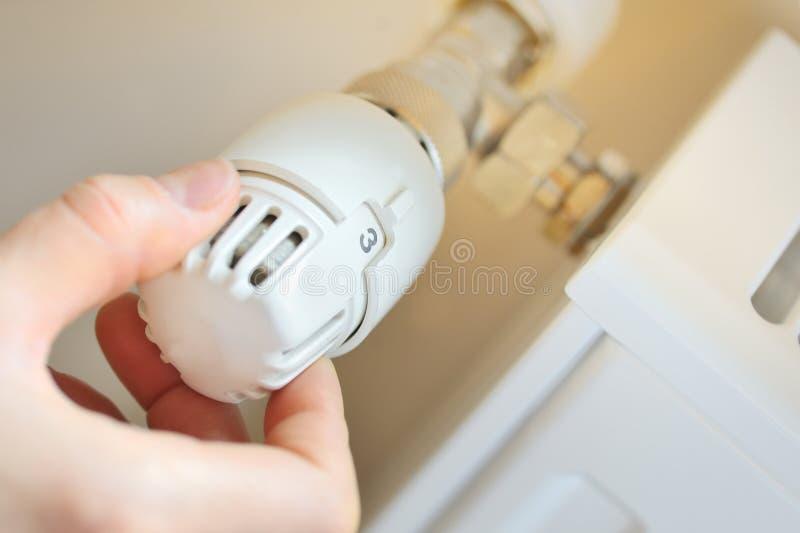 La mano registra la valvola del termostato fotografia stock