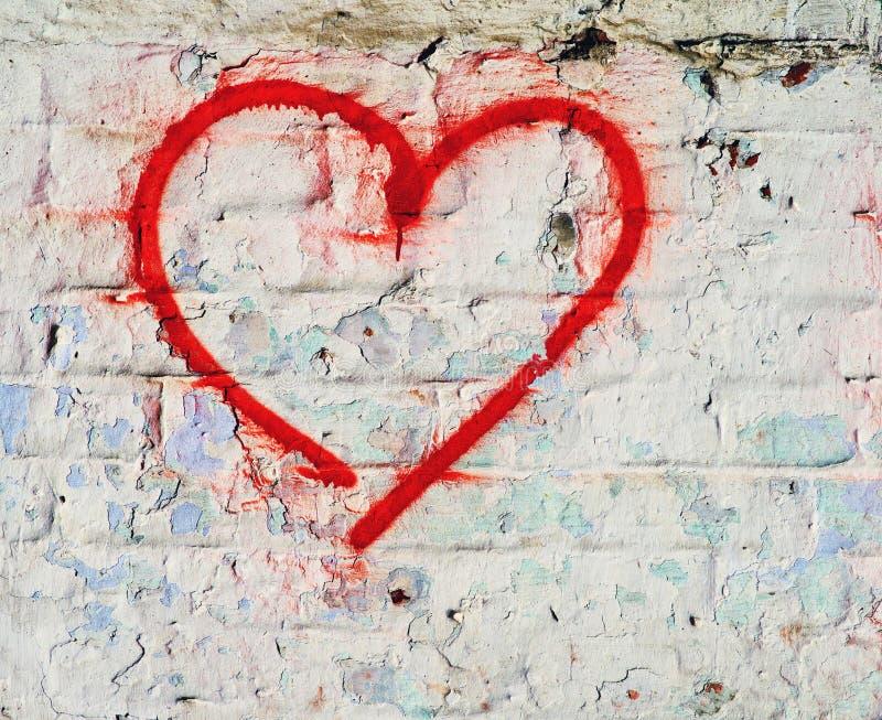 La mano roja del corazón del amor dibujada en grunge de la pared de ladrillo texturizó el fondo foto de archivo libre de regalías