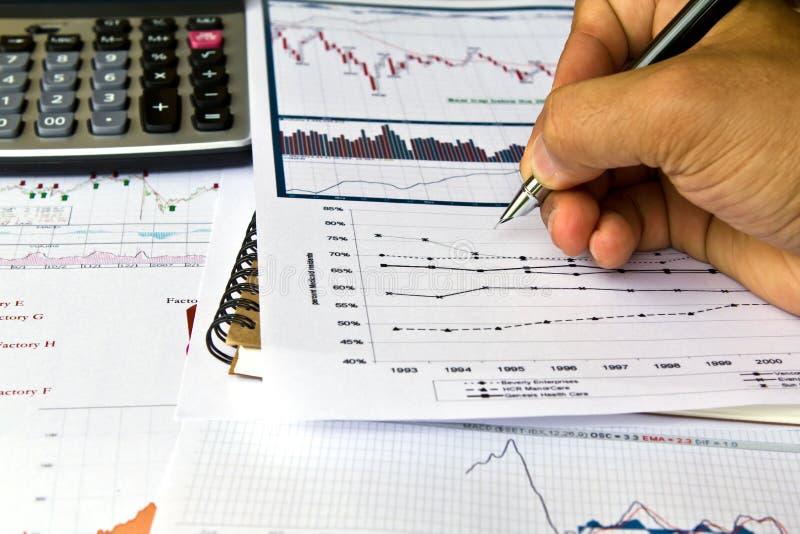 La mano scrive sui vari diagrammi finanziari immagine stock libera da diritti