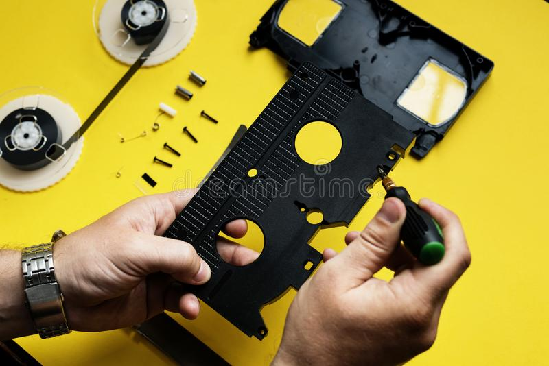 La mano separa le parti di videotape a parte fotografia stock