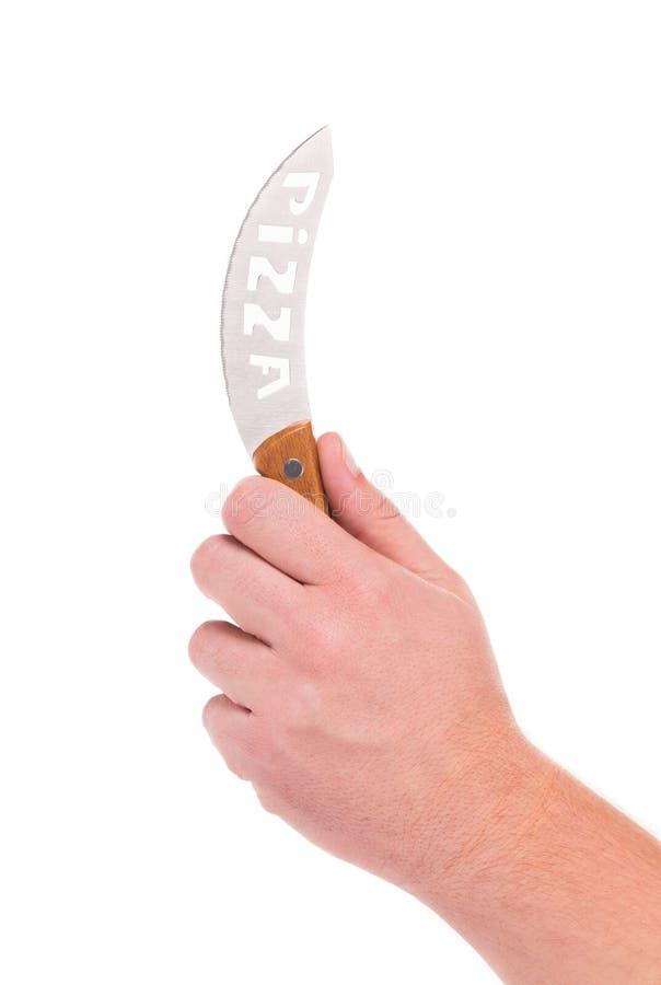 La mano sostiene el cuchillo de la pizza foto de archivo libre de regalías