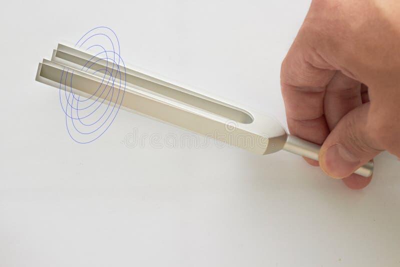 La mano sostiene el diapasón para la prueba del oído del doctor ENT o del fabricante de la onda acústica en el fondo blanco con l imagenes de archivo