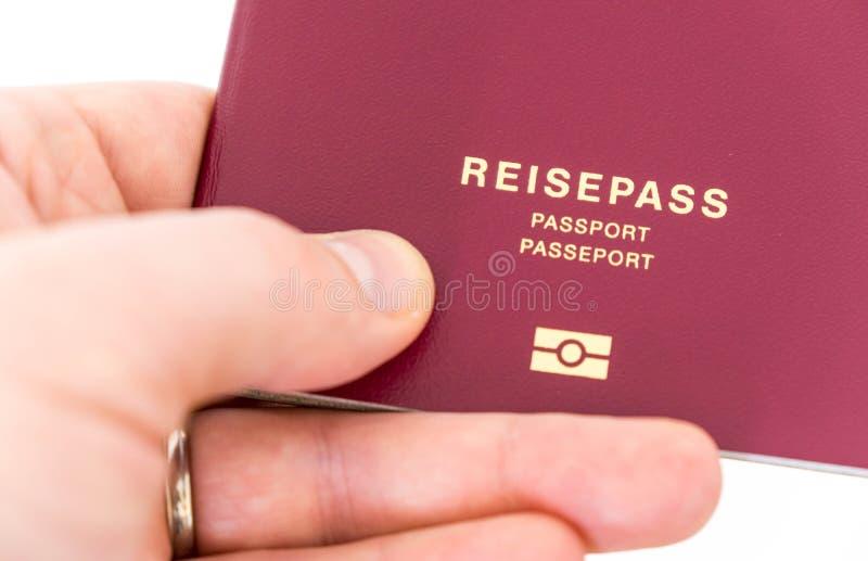 La mano sostiene el pasaporte alemán imágenes de archivo libres de regalías