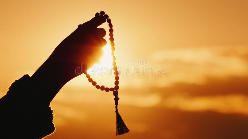 La mano sostiene el rosario contra el cielo y el sol poniente, el rezo sincero y la meditación imagen de archivo