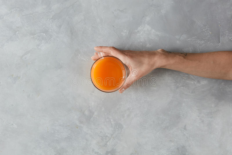 La mano sostiene el zumo de naranja fotos de archivo libres de regalías