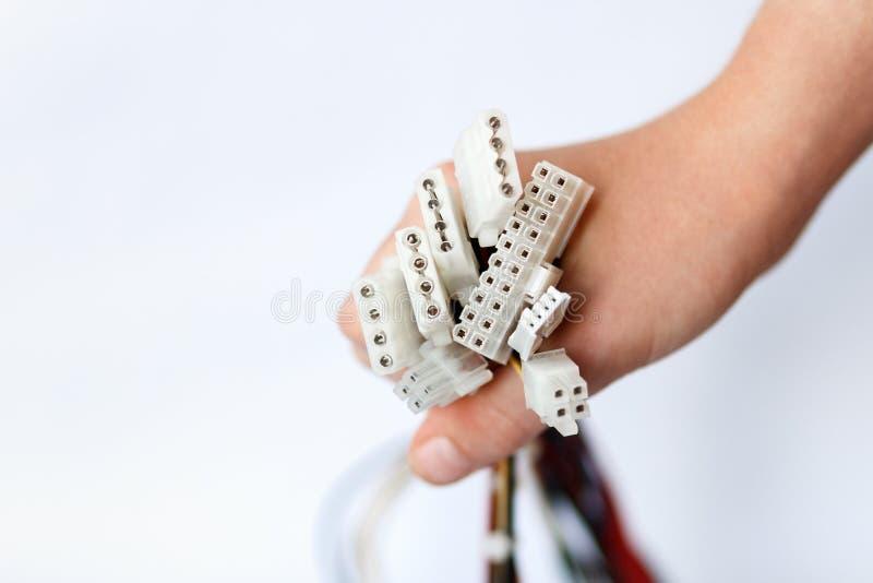 La mano sostiene los cables de transmisión de la unidad de la fuente de alimentación en los cables de transmisión blancos del fon fotos de archivo