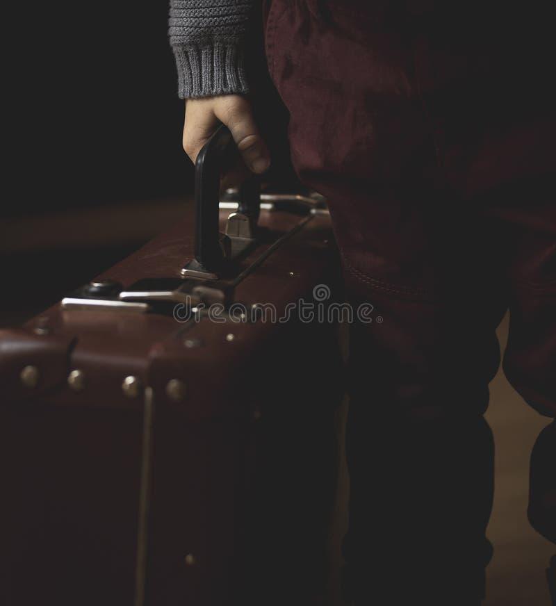La mano sostiene la maleta retra del marr?n del vintage Mirada de la c?mara Fotograf?a oscura foto de archivo libre de regalías