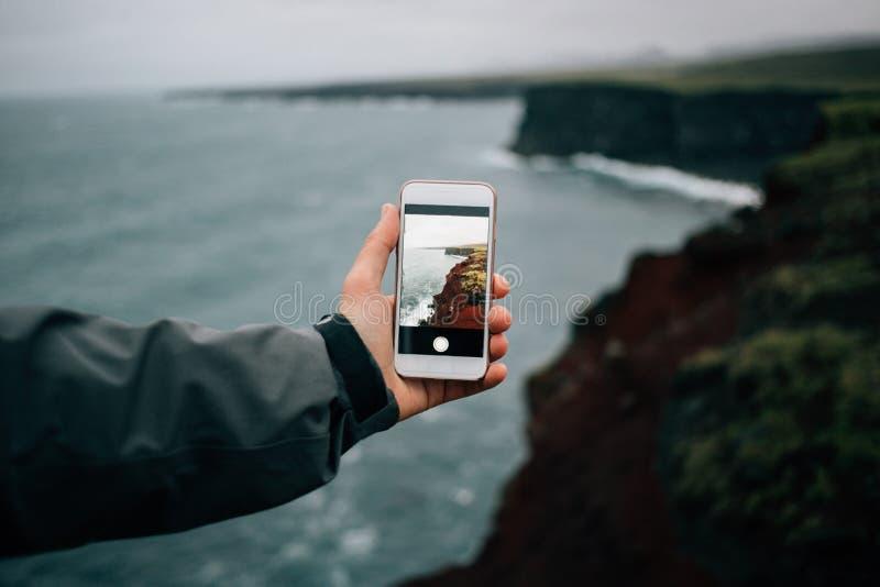 La mano sostiene smartphone para hacer la foto de paisaje fotos de archivo libres de regalías