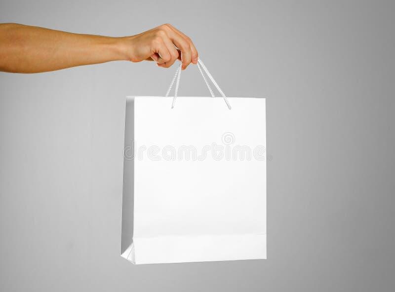 La mano sostiene un bolso blanco del regalo imagenes de archivo