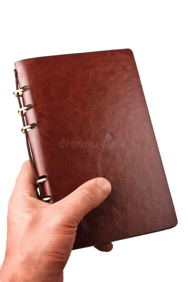 La mano sostiene un cuaderno de cuero imagen de archivo