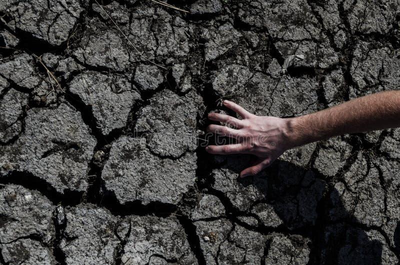 La mano sostiene un desierto agrietado imagen de archivo libre de regalías