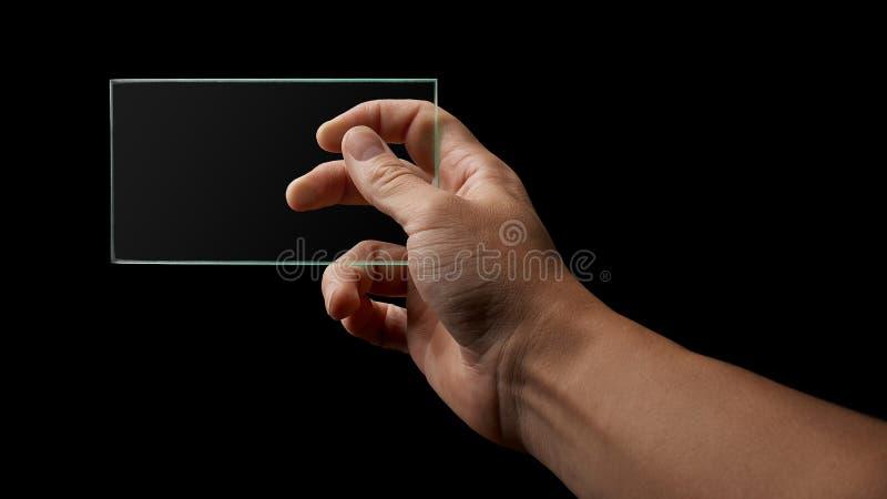 La mano sostiene un vidrio transparente foto de archivo