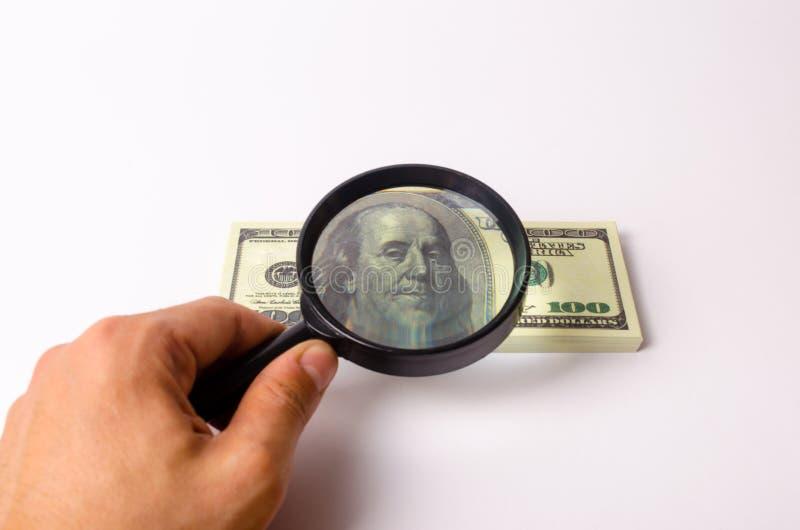 La mano sostiene una lupa y mira una cuenta de cientos dólares Céntrese el retrato de Franklin en la cuenta imagen de archivo libre de regalías