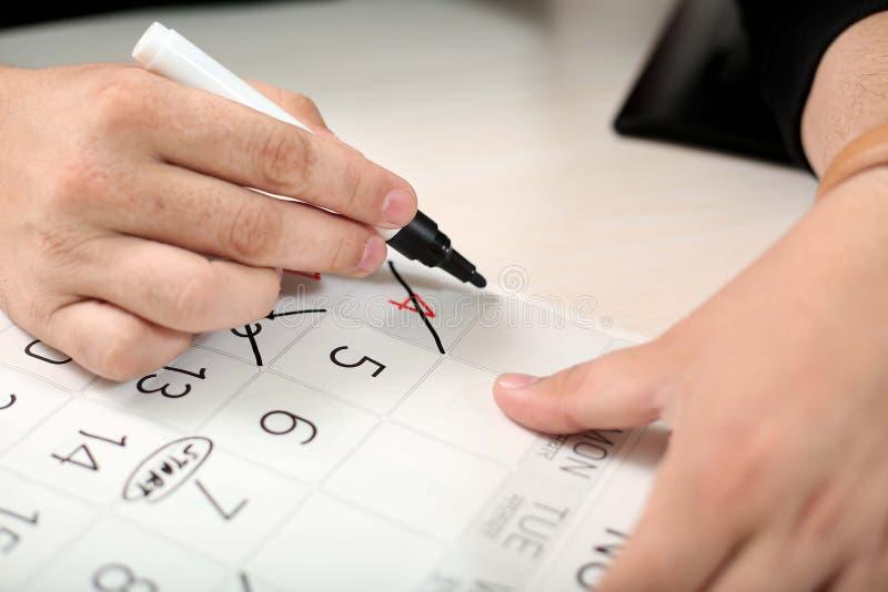 La mano sta segnando i giorni liberi trasversali l'indicatore nero nel calendario fotografia stock