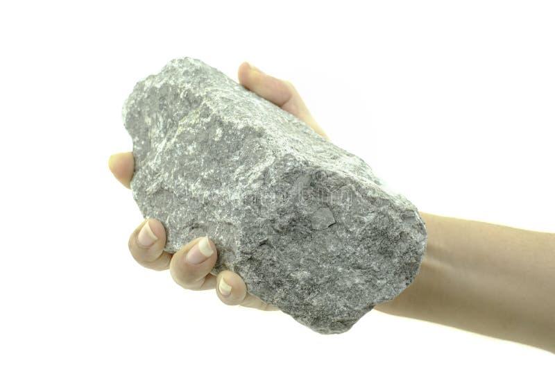 La mano stretta tiene la pietra su fondo bianco fotografie stock libere da diritti