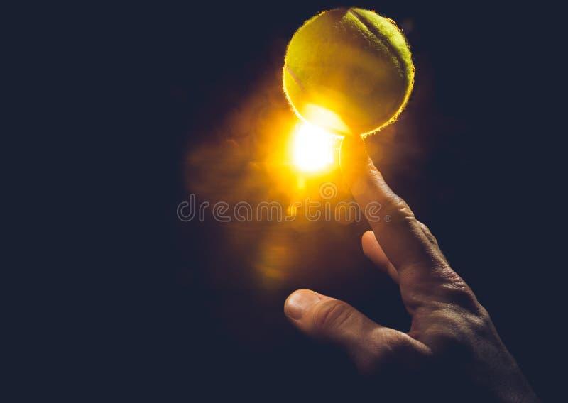 La mano su un fondo bianco schiaccia una pallina da tennis fotografia stock