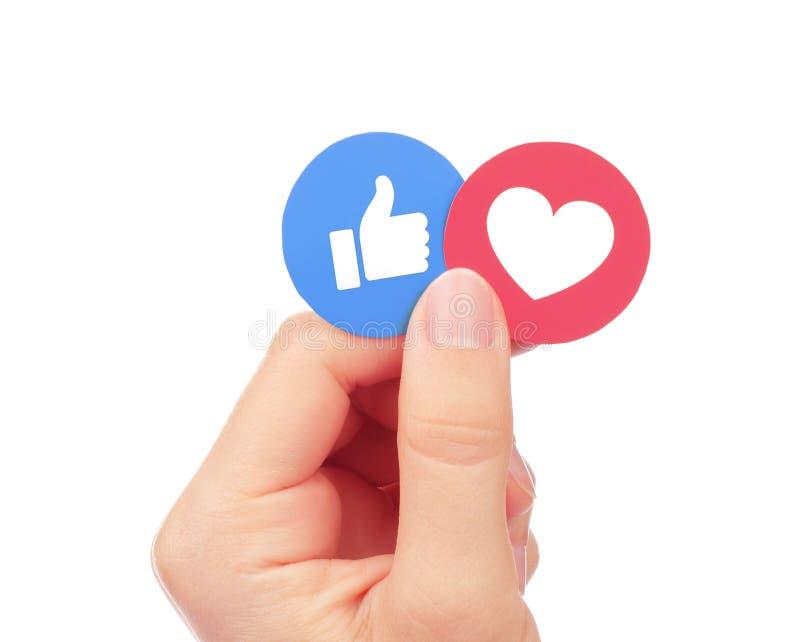 La mano tiene Facebook come e le reazioni comprensive di Emoji di amore fotografia stock