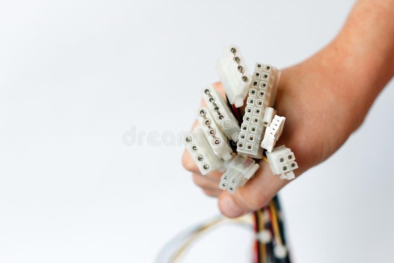 La mano tiene i cavi elettrici dall'unità di alimentazione sui cavi elettrici bianchi della scheda madre del PC, del fondo e sui  fotografia stock