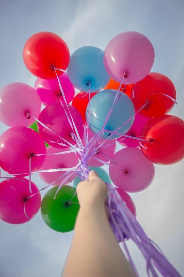 La mano tiene i palloni nel cielo immagine stock libera da diritti