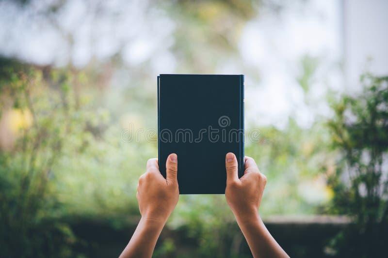 La mano tiene il libro su sopra la testa Concetti educativi fotografie stock libere da diritti