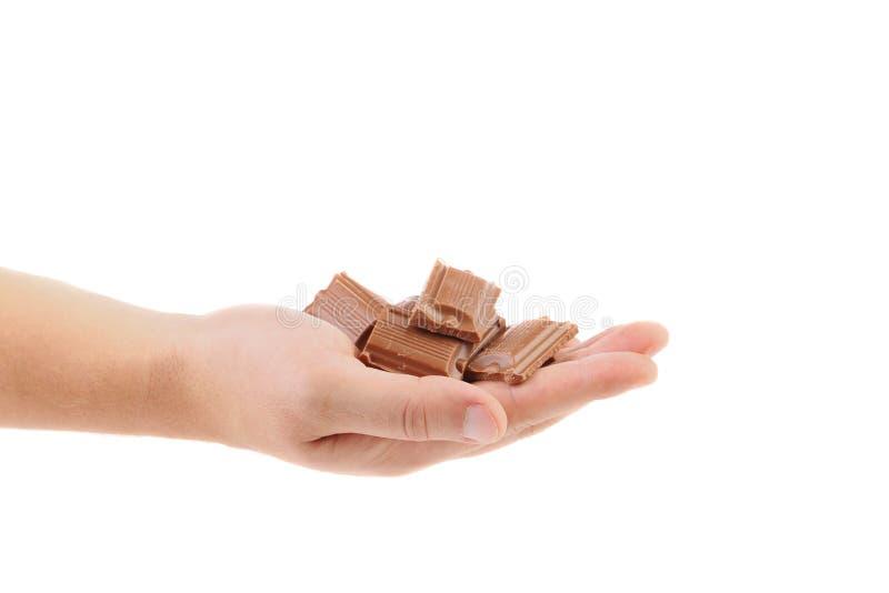La mano tiene il pezzetto saporito di cioccolato al latte. fotografia stock libera da diritti