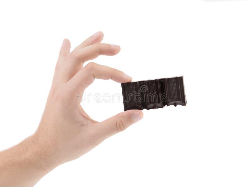 La mano tiene il pezzetto saporito di cioccolato fondente. fotografia stock