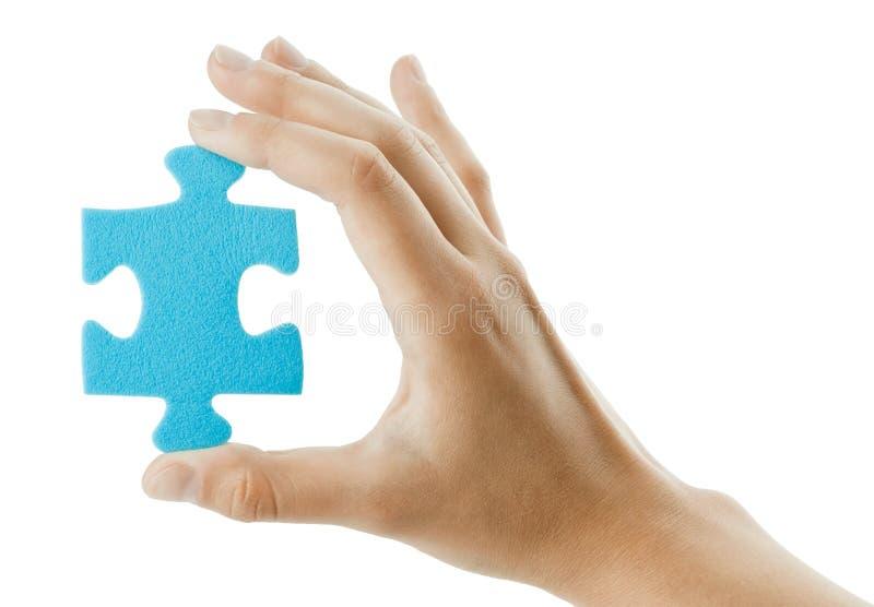 La mano tiene il puzzle fotografia stock