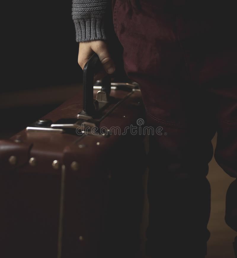 La mano tiene la retro valigia marrone d'annata Esaminando macchina fotografica Fotografia scura fotografia stock libera da diritti