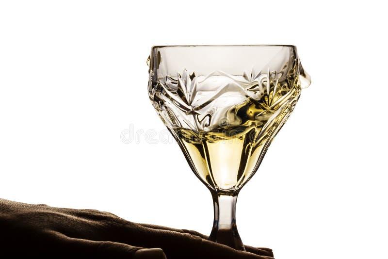 La mano tiene un vetro di vino luminoso bianco fotografie stock