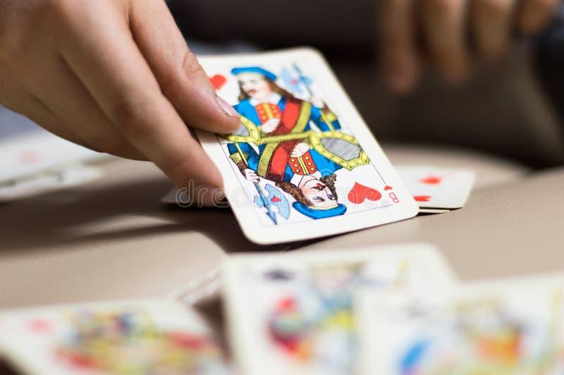 La mano tiene una carta da gioco fotografia stock
